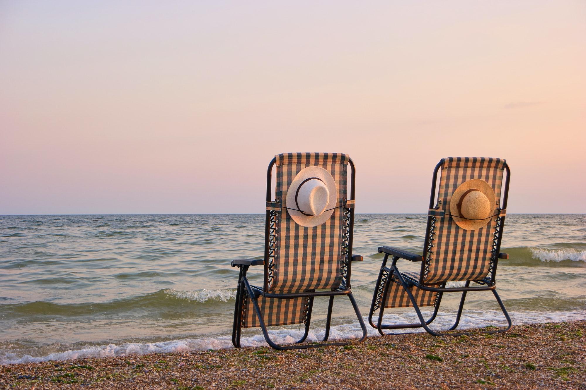 Deck chairs on a beach.
